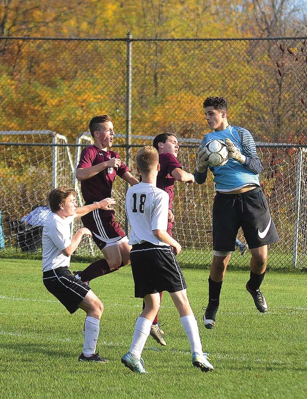 Oppenheim-Ephratah/St. Johnsville goalkeeper Elias Sanchez grabs a cross in front of Loundonville Christian's Noah Rogers and SamuelJack Provencher as the Wolfpack's Robert Snell and Max Christensen (18) back up the play during a Section II Class D semifinal match on Oct. 25 at Oppenheim-Ephratah/St. Johnsville High School. (The Leader-Herald/James A. Ellis)