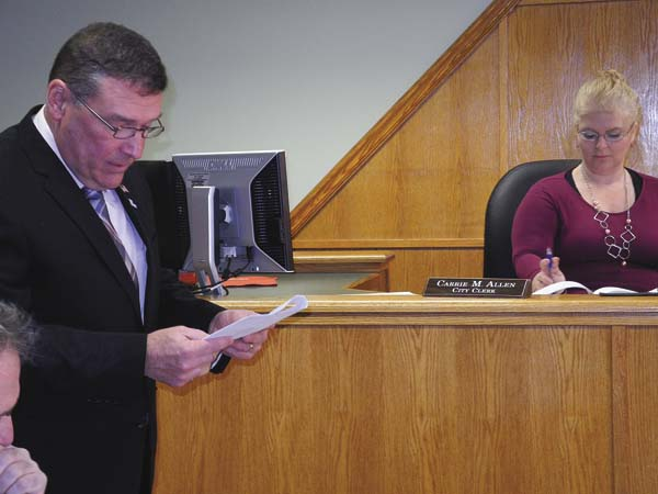 Johnstown Councilman-at-Large Craig Talarico, standing, reads a resoution appointing Carrie Allen, in the background, as new Johnstown city clerk at the Johnstown Common Council's organizational meeting Monday at City Hall. (The Leader-Herald/Michael Anich)