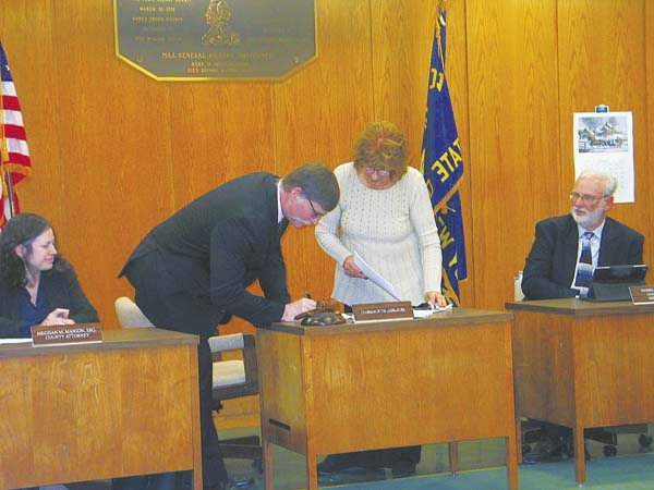 District 4 Legislator Robert Headwell, Jr. signs as he was elected as chairman for the Montgomery County Legislature during the organizational meeting Tuesday night. Standing to the left of him is Montgomery County Clerk Helen Bartone. (The Leader Herald/Briana O'Hara)