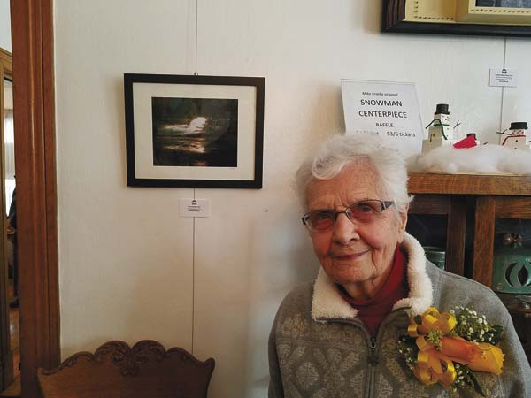 Norma Porteus stands next to one of her photographs. (For The Leader-Herald/Greg Hitchcock)