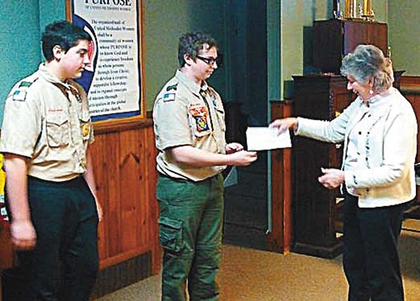 Members of Broadalbin Boy Scout Troop 5051, from left, Chris Buelow and Shain Krutz give $690 check to Sue Moyer of the Ecumenical Food Pantry at Broadalbin  United Methodist Church on Jan. 2. The donation to the pantry represents the October portion of the troop's year-round bottle drive. (Photo submitted)