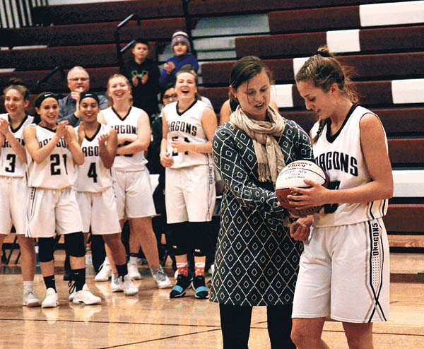 Gloversville girls varsity Coach Molly D'Arcy presents Harmony Philo with a basketball commemorating her reaching the 1,000-point career scoring milestone with 10.1 seconds left in the first of of the Lady Dragons Foothills Council game against Glens Falls Monday at Gloversville High School. (The Leader-Herald/James A. Ellis)