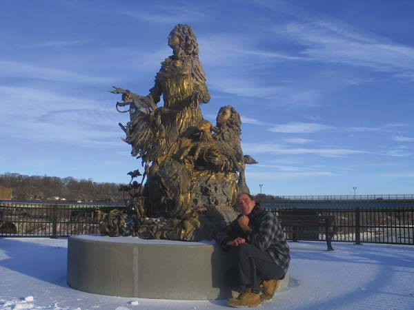 """Artist Dimitar Lukanov poses next to the sculpture, """"Mother and Child at the Mohawk River"""" he sculpted for the Mohawk Valley Gateway Overlook pedestrian bridge, which was installed on Thursday. (The Leader-Herald/Briana O'Hara)"""
