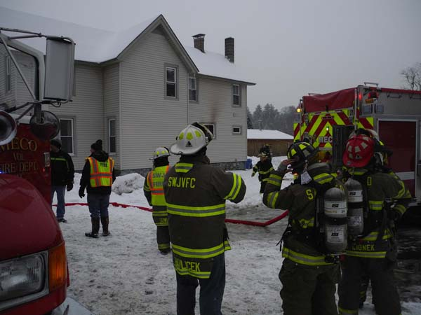 Volunteer firefighters talk during a fire to the rear of a home at 185 County Highway 101 in Meco Tuesday afternoon. (The Leader-Herald/Michael Anich)