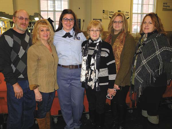 Johnstown postal carrier Nicole Hunt, third from left, poses with the woman she saved, Judi Gosselin, fourth from left. Other family pictured from left are: Gosselin's son-in-law and daughter, Aaron and Evamarie Mraz; and Tina Morey, another Gosselin daughter; and Karen Stowell, Hunt's mother. (The Leader-Herald/Michael Anich)