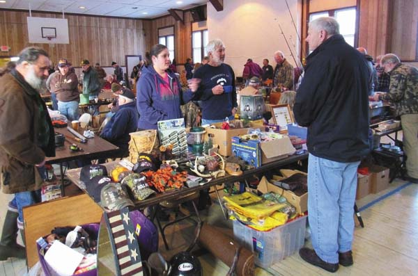 The public examines wares at the annual Sportsman Swap Meet Saturday at the Wells Community Center on Route 30, sponsored by the Wells Fish and Game Club. (The Leader-Herald/Eric Retzlaff)