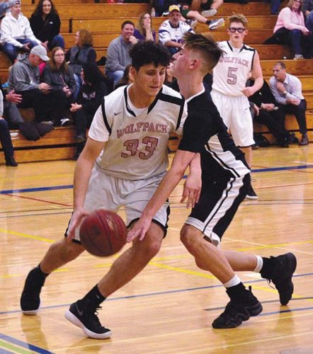 Oppenheim-Ephratah/St. Johnsville's Zach Mosher (5) looks on as the Wolfpack's Elias Sanchez muscles his way along the baseline against Herkimer's William Startk at the SectionII/Section III Challenge Sunday at Fulton-Montgomery Community College. (The Leader-Herald/James A. Ellis)