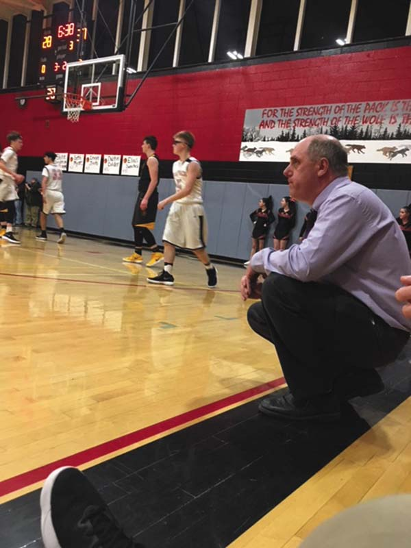 Oppenheim-Ephratah/St. Johnsville boys basketball coach Jason Brundage watches from the sideline during Friday's Western Athletic Conference game against Canajoharie. The Wolfpack won 76-65 as Brundage collected his 200th career victory. (Photo submitted)