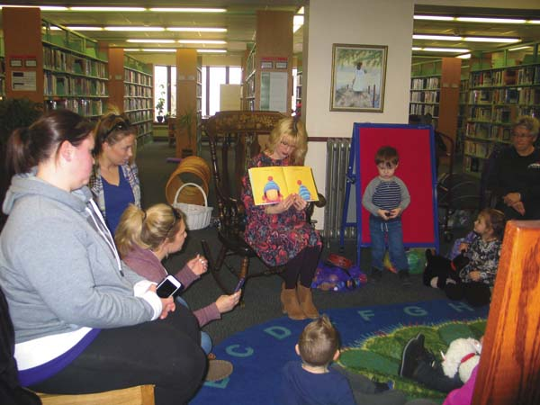 Katie Stevens, Youth Media Services Specialists reads to children at the Amsterdam Free Public Library on Monday. (The Leader-Herald/Briana O'Hara)