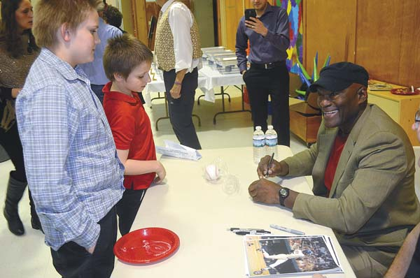 Former major league ball player George Foster, right, smiles as he talks with and autographs a baseball for Christopher Moore II, left, and William Moore of Hagaman at the 11th annual Mohawks Hot Stove banquet Saturday night at St. Mary's Institute in Amsterdam. (The Leader-Herald/James A. Ellis)