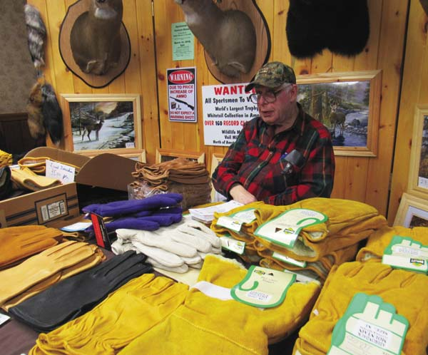 Bob Kazmierski, director of the Wildlife Museum in the town of Ansterdam, is selling gloves and other items as a fundraiser for the museum at the 13th annual Adirondack Outdoorsman Show Saturday at the Moose Lodge in Johnstown. (The Leader-Herald/Eric Retzlaff)