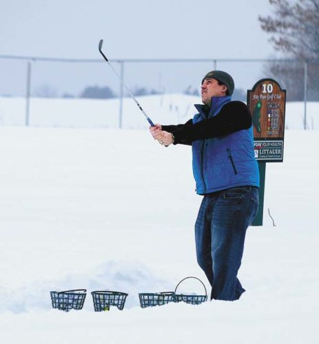 Dan Houtz follows the flight of his chip shot at the Closest to the Pin competition Saturday at Fox Run Golf Club.