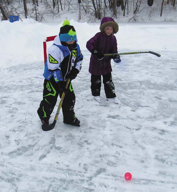 Landon Conyne, 8, left, and his sister, Kendyl, 6, compete in ice hockey, one of the games for youths at the annual Community Winter Carnival at Mayfield Lake Saturday. (The Leader-Herald/Eric Retzlaff)