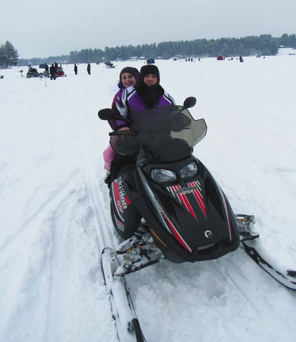 Brenda Van Every gives Elyssa Van Every, 11, a snowmobile ride at the annual Community Winter Carnival at Mayfield Lake Saturday. The snow-covered ice was reportedly 24 inches thick. (The Leader-Herald/Eric Retzlaff)