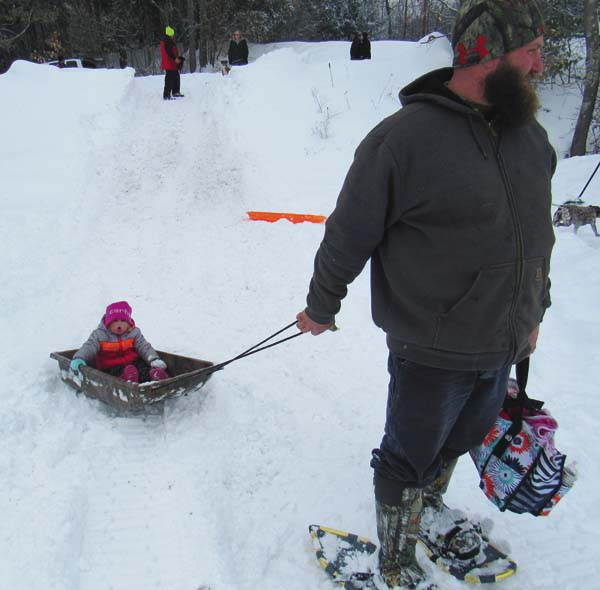 Kinlee, 2, gets a ride from her dad, Mark Savoie of Mayfield, at the annual Community Winter Carnival at Mayfield Lake Saturday. Savoie said he takes her and his son, Brodie, 7, fishing at the event every year. (The Leader-Herald/Eric Retzlaff)