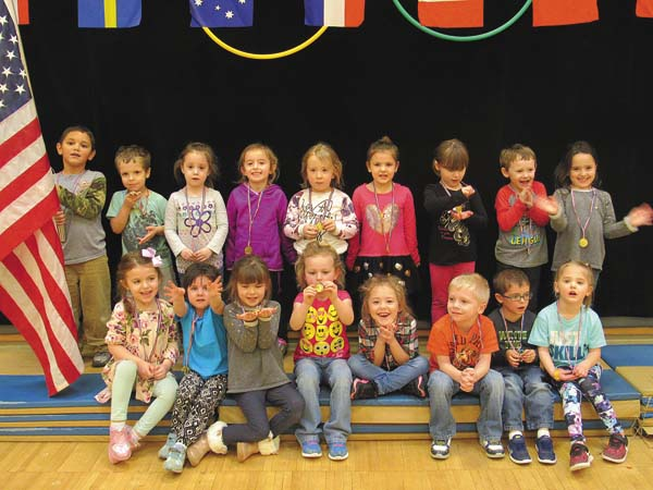 Students in Mary Jo Lomanto's pre-k class at Kingsborough Elementary School pose on the Olympic podium after receiving gold medals Thursday in the school gym. (The Leader-Herald/Ashley Onyon)