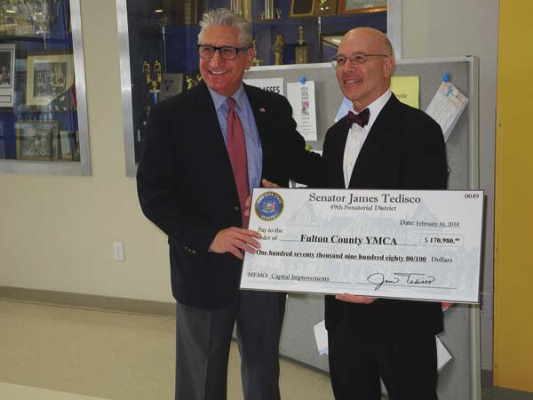 State Sen. James Tedisco, R-Glenville, left presents a check for $170,980 to Fulton County YMCA CEO Steven Serge Friday morning a the facility. The check represents a state grant award to the YMCA for various projects being done by the facility this year. (The Leader-Herald/Michael Anich)