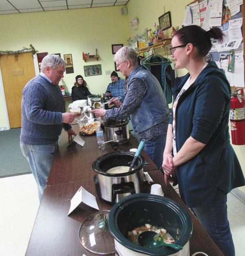 The Rev. Ralph English, pastor of the First Congregational United Church of Christ of Gloversville, is served soup from Lenora Evans of Gloversville, center, and Kimberlee Harden of Fonda at the third annual Soupurr Cookoof Saturday at the Gloversville Senior Center. The event benefitted the Cat Sanctuary and Information Center. (The Leader-Herald/Eric Retzlaff)