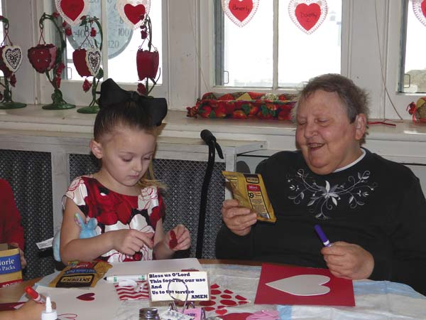 Photo courtesy of Tammy Kruger   Emilia Montano, left, from Ms. Bobbi Jo's preschool class , and Phyllis  right enjoy making a Valentines Day card at the Willing Helpers Home in Johnstown on Wednesday. The pre school  class  from Ms. Bobbi Jo's  morning group  came to Home on Valentines Day for a craft project of making Valentines. (Photo submitted)