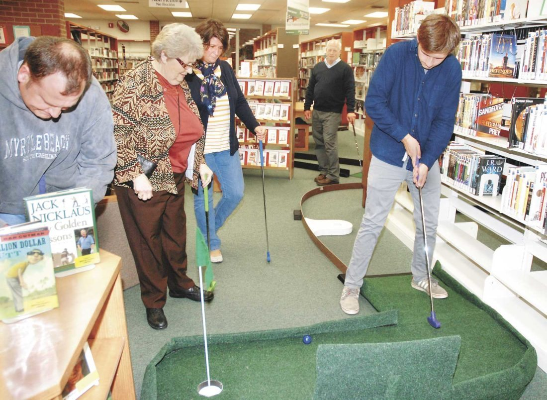 Sentinel photo by BUFFIE BOYER Aaron Sherwood, right, of McClure hits the ball during a game of miniature golf as, from left, Jim Sherwood, Geraldine Gerber, Rachel Sherwood and Jeff Ingram watch Friday evening at the Mifflin County Library. The library's inaugural 'Putting for Pages' event, sponsored by Geisinger and Thrivent Financial, is a fundraiser for the library. The event continues from 9 a.m. to 4 p.m. today for families and costs $5 per person.