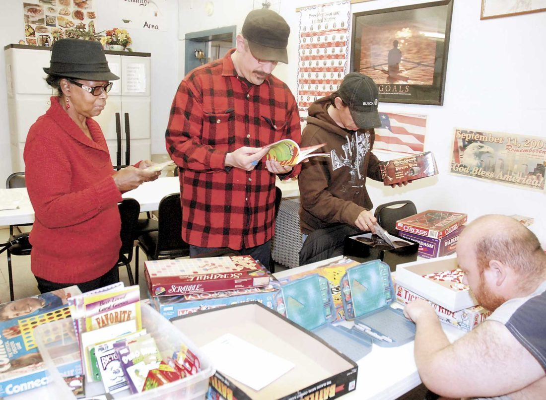 Sentinel photo by BUFFIE BOYER Sunshine Connection Director Pat Johnson, from left, and consumers Shawn Corson, Gerald Woodring and Dan O'Donnell, look over games Tuesday that were donated to the drop-in center.