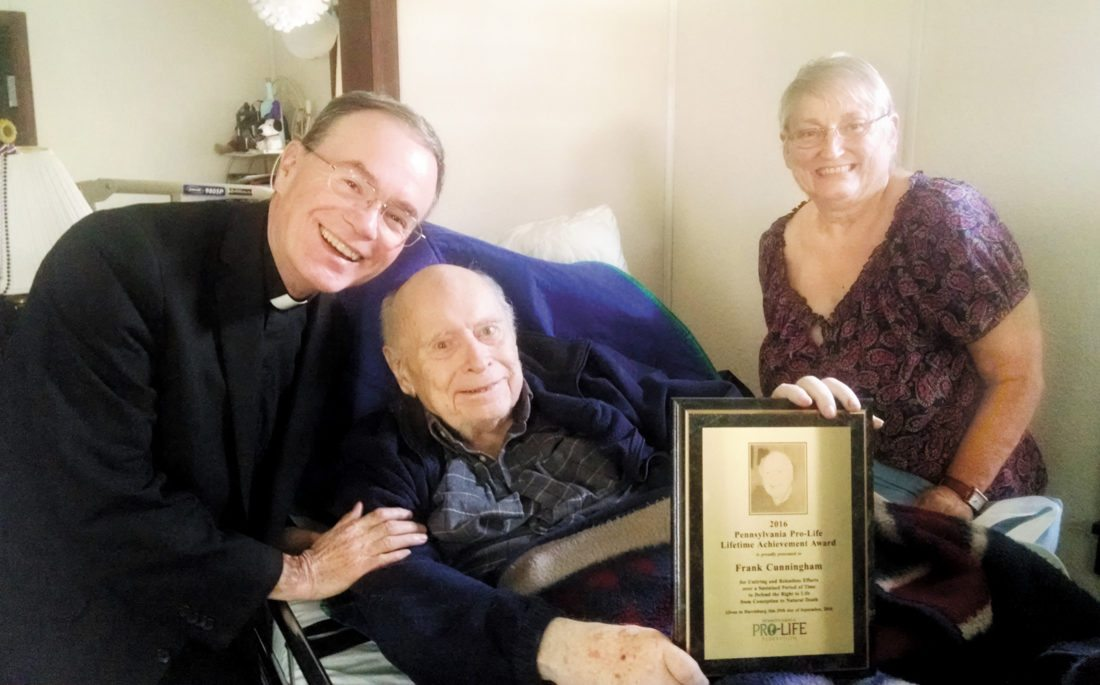 Photo submitted by FATHER WILLIAM WEARY Frank Cunningham, Milroy, center, holds the Lifetime Achievement Award, presented to him at the annual banquet of the Pennsylvania Pro-Life Federation, Sept. 29, at the Radisson Penn Harris Convention Center, Camp Hill. Michael Bailey, owner of Burnham OIP, offered the banquet invocation before about 600 attendees. Since Cunningham was unable to attend the event due to health issues, the award was received at the banquet by his pastor, Father William M. Weary, the pastor of the Sacred Heart of Jesus Catholic Church, who here presents the plaque to the awardee at his home. Cunningham organized many Lewistown area pro-life events over the last 12 years or more, including the annual Life Chain October rally on the Mifflin County Courthouse steps and the Pro-Life March through the streets of Lewistown every January in protest against the legalization of abortion. Pictured also is Jane Brown, the awardee's sister and caregiver.