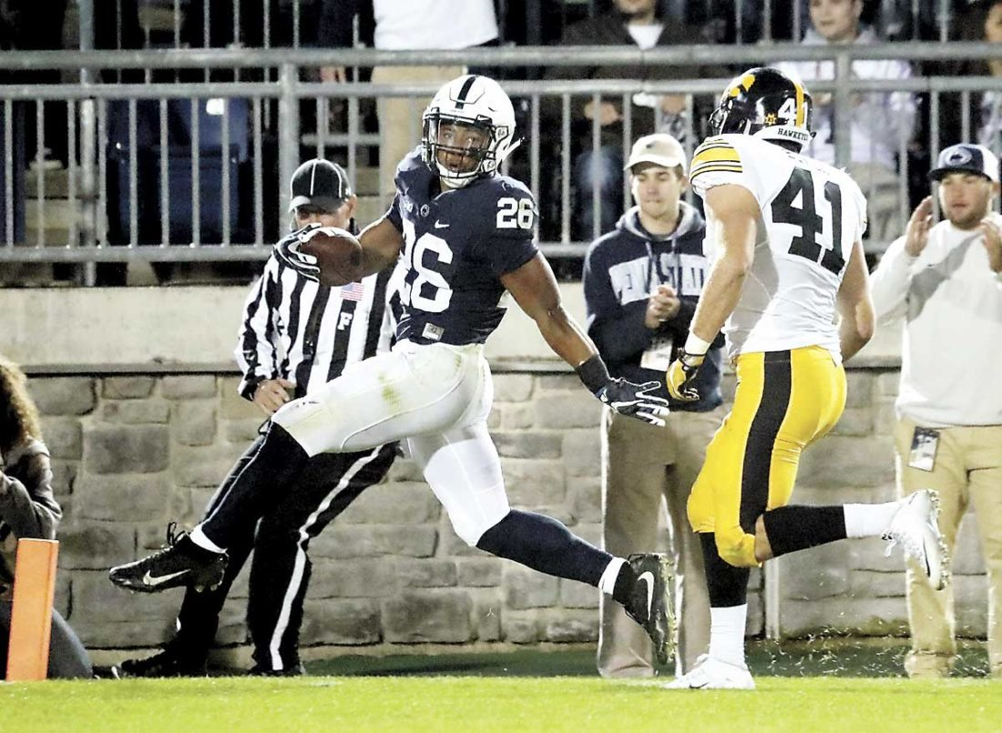 Sentinel photo by CHRISTOPHER SHANNON  Penn State's Saquon Barkley celebrates as he crosses the goal line in front of Iowa's Bo Bower during the  Nittany Lions' 41-14 victory over the Hawkeyes  Saturday night, at Beaver  Stadium.