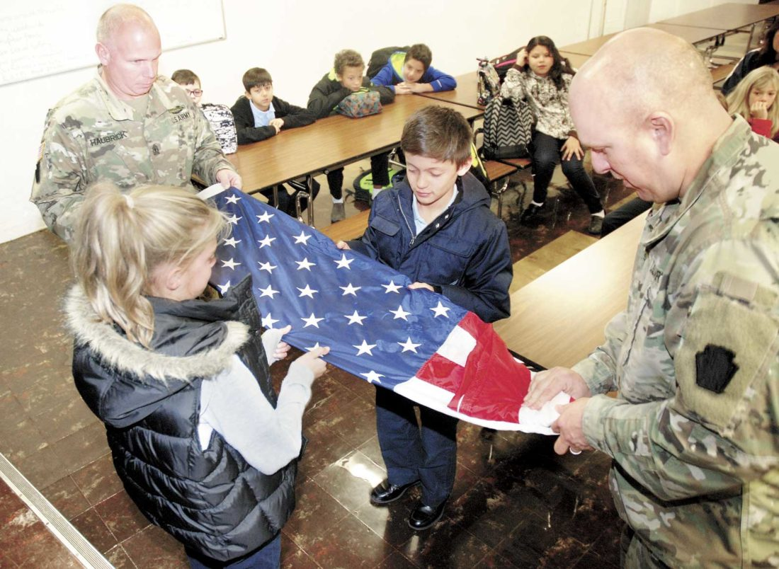 Sentinel photo by BUFFIE BOYER First Sgt. Dave Haubrick, far left, and Sgt. 1st Class Marlin Manbeck, right, show Sacred Heart School students Tressie Bender, left, and Farrel Souders how to properly fold an American flag Tuesday,  during a Veterans Day program at the school in Lewistown. The soldiers spoke to the whole school about their time in Iraq and answered questions from the students.