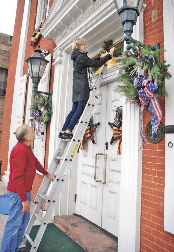 Sentinel photo by BUFFIE BOYER Sandy Knapik, top, places greens and bells atop the front doors Wednesday, at the Historic Courthouse in Lewistown while her husband, Dennis, holds the ladder. The Knapiks were asked to decorate the courthouse with an Americana holiday theme for the Veterans Day parade today and for the Festival of Ice in December since this year's theme is 'Honoring our Military.'