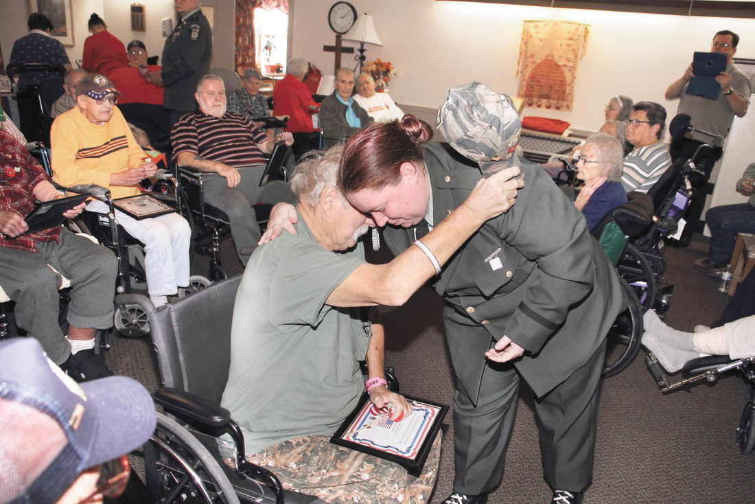 Sentinel photo by MATT STRICKER Veterans of Foreign Wars Post 7011 Honor Guard member Jean Bonson gives a hug to veteran John Wileman while thanking him for his service during a Veterans Day recognition ceremony held Friday at William Penn Healthcare and Rehabilitation Center in Lewistown.  Wileman served in the U.S. Army, stationed in Vietnam from 1969-1970, as well as spending 19 years in the Army Reserve. Wileman is a resident of William Penn.