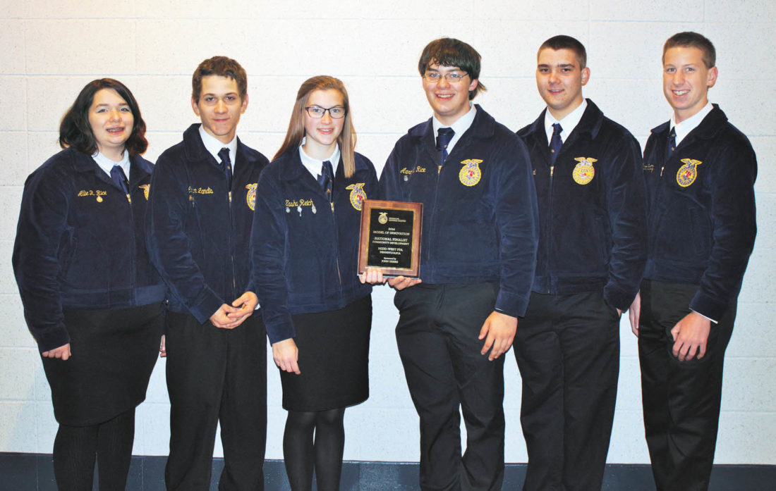 Submitted photo Midd-West FFA students stand together with the plaque awarded to the organization during the National FFA convention in October in Indianapolis.