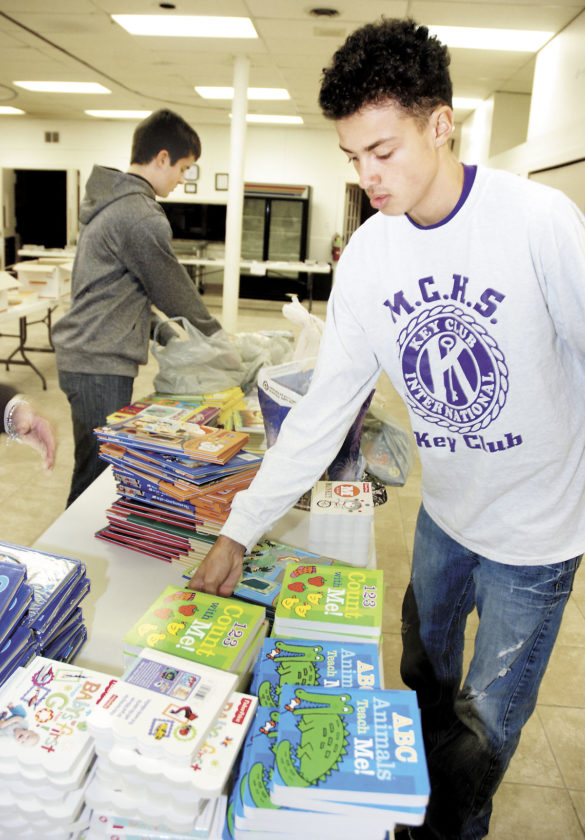 Andrew Willard, left, and Julian Jackson, both members of the Mifflin County High School Key Club, sort through bags of new books Monday at the Santa's Bookbag program at Grace United Methodist Church. This is the 25th year for the program, which provides at least four to five gently used books and one new book to children in need. This year so far, 450 children will be given books this Christmas. The Salvation Army provides the names of the children who need books and if a child requests a certain title or type of book, the program makes its best effort to fulfill that request. Students from MCHS' Key Club and National Honor Society and members of the Mifflin County Chapter of Pennsylvania Association of School Retirees, help each year to sort and clean the books. Monetary donations are needed to purchase new books for next year's program. Send donations to The  Sentinel, 352 Sixth St.,  Lewistown, PA 17044.  Sentinel photo by BUFFIE BOYER