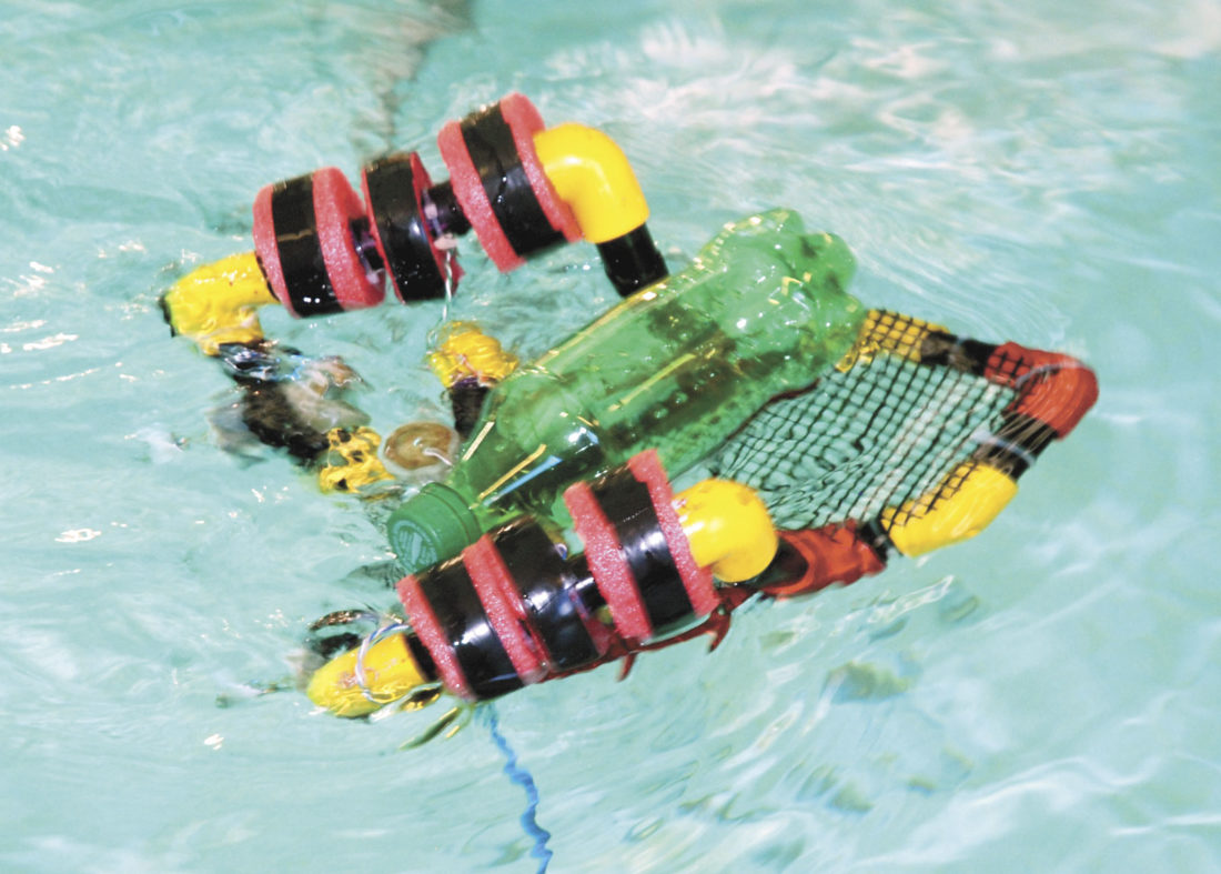 A robot carries a plastic bottle back to the edge of the swimming pool in the clean up challenge.