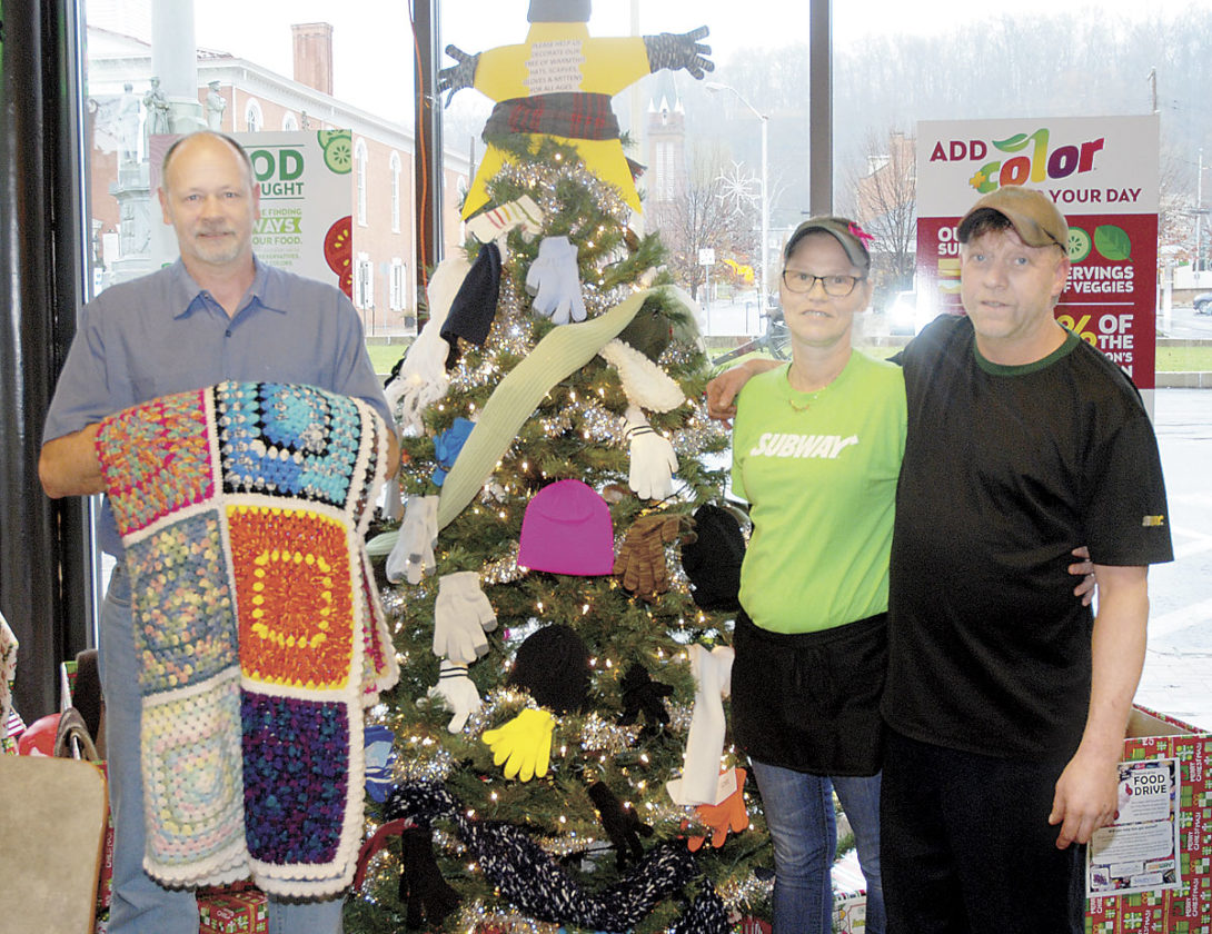 The Subway restaurant at Monument Square is holding its second Tree of Warmth to collect blankets, hats, coats, gloves and scarves to be donated to the Salvation Army. Customer Rich Seward, left, holds a donated blanket while Subway owners Amy Confer and Lloyd Cavanaugh show the tree covered in donated items. The restaurant is also working in conjunction with Ed's Trains, South Hills School of Business and Technology and the Juniata River Valley Chamber of Commerce with the Festival of Ice Food Drive. Donations of canned food items will be used to create holiday train displays at 3 W. Monument Square and at South Hills. Food will be given to Mother Hubbard's Cupboard. Donations are accepted during the Festival of Ice and throughout the holiday season.
