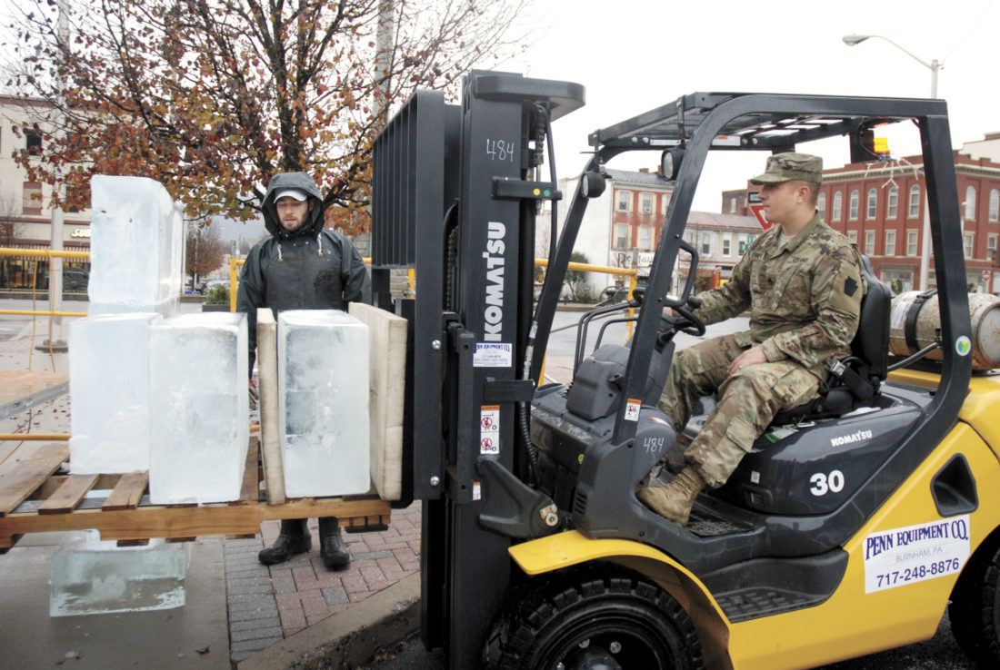 Sentinel photo by BUFFIE BOYER Staff Sgt. Ryan Bennett, right, of the National Guard, delivers a load of ice blocks to Jared McAlister, of DiMartino Ice, Wednesday afternoon in preparation to build an ice wall for the Festival of Ice, which starts today.