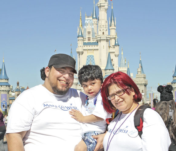 Submitted photo Parents Rafael Gomez, left, and Keila Cintron, right, don their matching Make-A-Wish T-shirts with their son, Aiden, in front of Cinderella's Castle in the Magic Kingdom at Walt Disney World in Orlando, Fla.