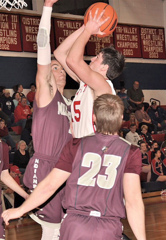 Sentinel photo by BROOKE FOSTER  Juniata's Tyler Clark, center, shoots for two as Millersburg's Matt Snyder, left, and Cole Shomper (23) try to block the shot Wednesday evening in Mifflintown.