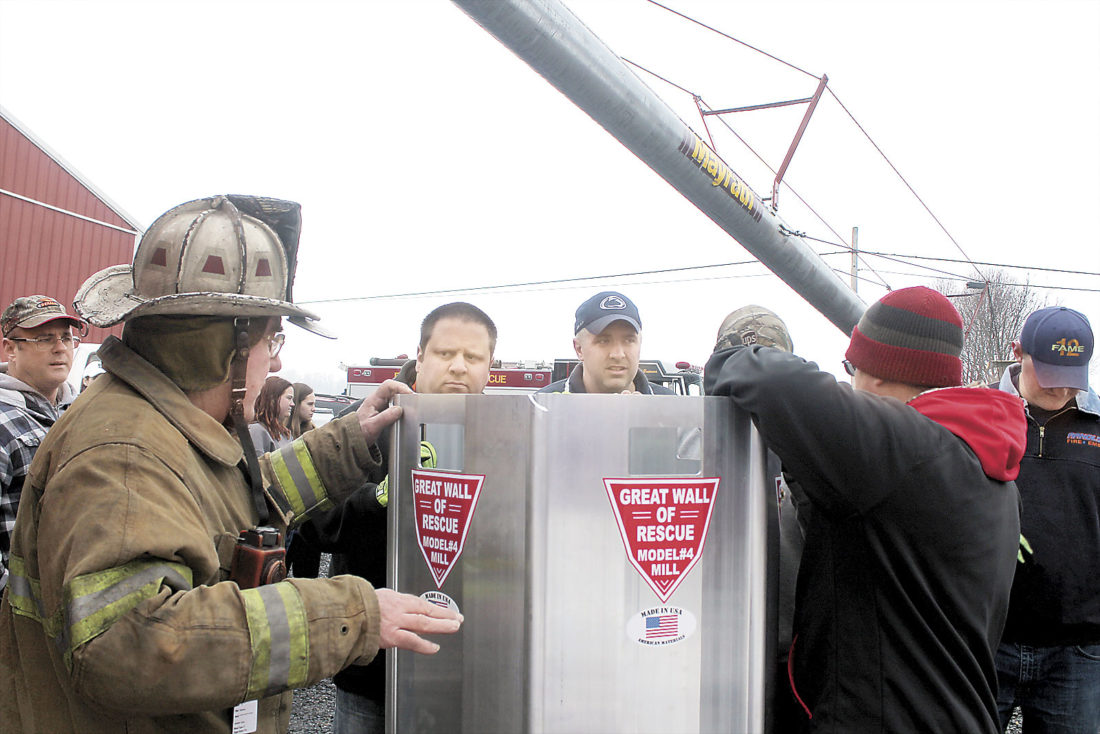 Sentinel photo by LAUREN KERSHNER  Lewistown Borough Fire Department Safety Officer Bob McCaa teaches a group of City Hook and Ladder firefighters how to put together a tool to rescue someone who is trapped in a grain silo or bin on a farm. The grain rescue tube was purchased through a grant from the Land O'Lakes Foundation.