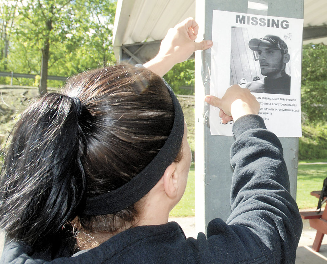 Sentinel photo by BUFFIE BOYER  Amanda Marker, of Lewistown, hangs a poster at Rec Park Tuesday asking the public to help find Shane  Workman who has been missing since April 25.
