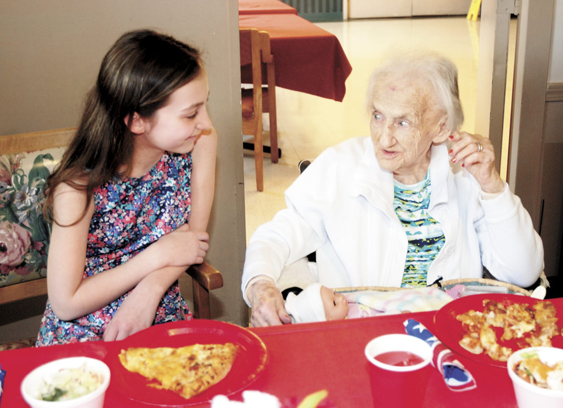 Sentinel photo by BUFFIE BOYER  Olivia Kahley, left, a member of the Husky Helpers Club at Mifflin County Middle School, visits with William Penn Nursing Home resident Dorothy Philips Thursday in Lewistown, during a pizza party to celebrate the last visit of the school year. The 30  students have been visiting the residents twice a month since the beginning of the school year to socialize, play games, take residents outside for fresh air and sing Christmas carols.