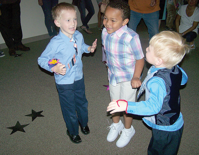 Photos submitted by BLANCHE BOGAR From left, preschoolers Treyson Yohn, Jaylin Smalls, and Reece Hagerty enjoy the 'prom' event at Lewistown Children's Center. At the beginning of May enrolled families and Facebook friends were challenged to help the Lewistown Children's Center Facebook page reach 1,200 likes by the end of the month. Within a week the goal had been surpassed and prom planning had begun. The event was held Friday with more than 160 family members attending with their child(ren), bringing prom attendance to more than 300 children and families.