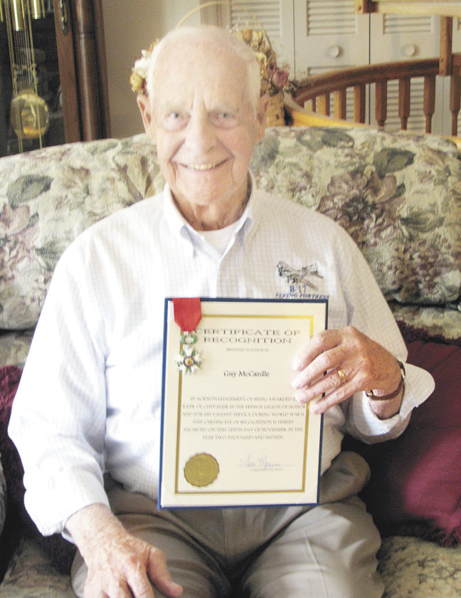 Sentinel photo by TABITHA GOODLING Guy R. McCardle, a 94-year-old resident of Burnham, sits in his living room holding his French Legion of Honor medal and certificate for his service in liberating France at the conclusion of World War II.