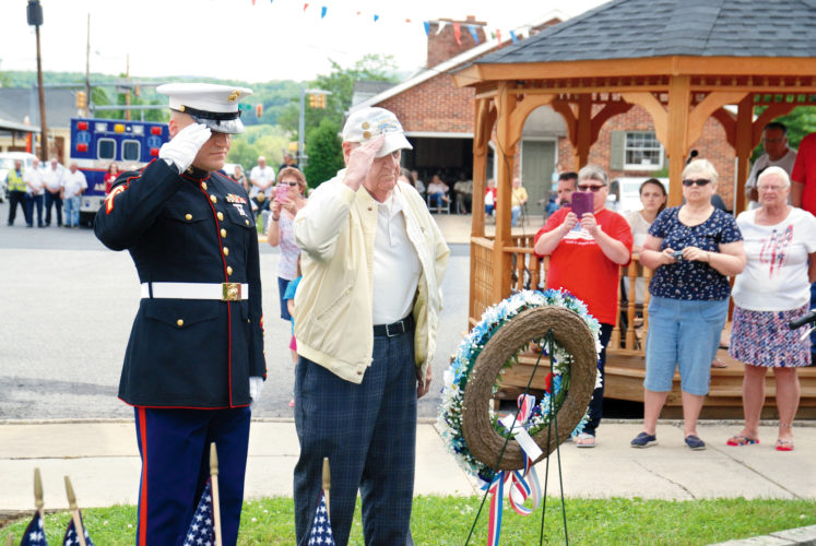 Sentinel photo by BRADLEY KREITZER WWII Army Air Corps veteran Tom Fletcher, right, and Lions Club member Rick Clark salute after placing a wreath at the McVeytown war memorial during a ceremony after the McVeytown Memorial Day parade Monday morning in McVeytown.