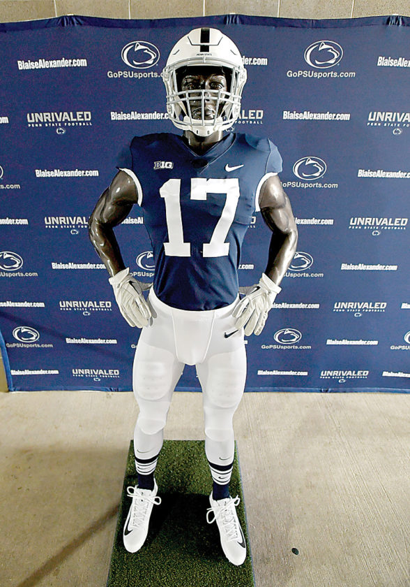 "Penn State football announced their ""generations of greatness"" uniform that the team will wear for the September 30 game against Indiana during a press conference on Thursday, June 15, 2017. White cleats like those worn in the 1979 Sugar Bowl and stripped socks the Nittany Lions wore from 1970-1972 are part of the uniform.  (Abby Drey/Centre Daily Times via AP)"
