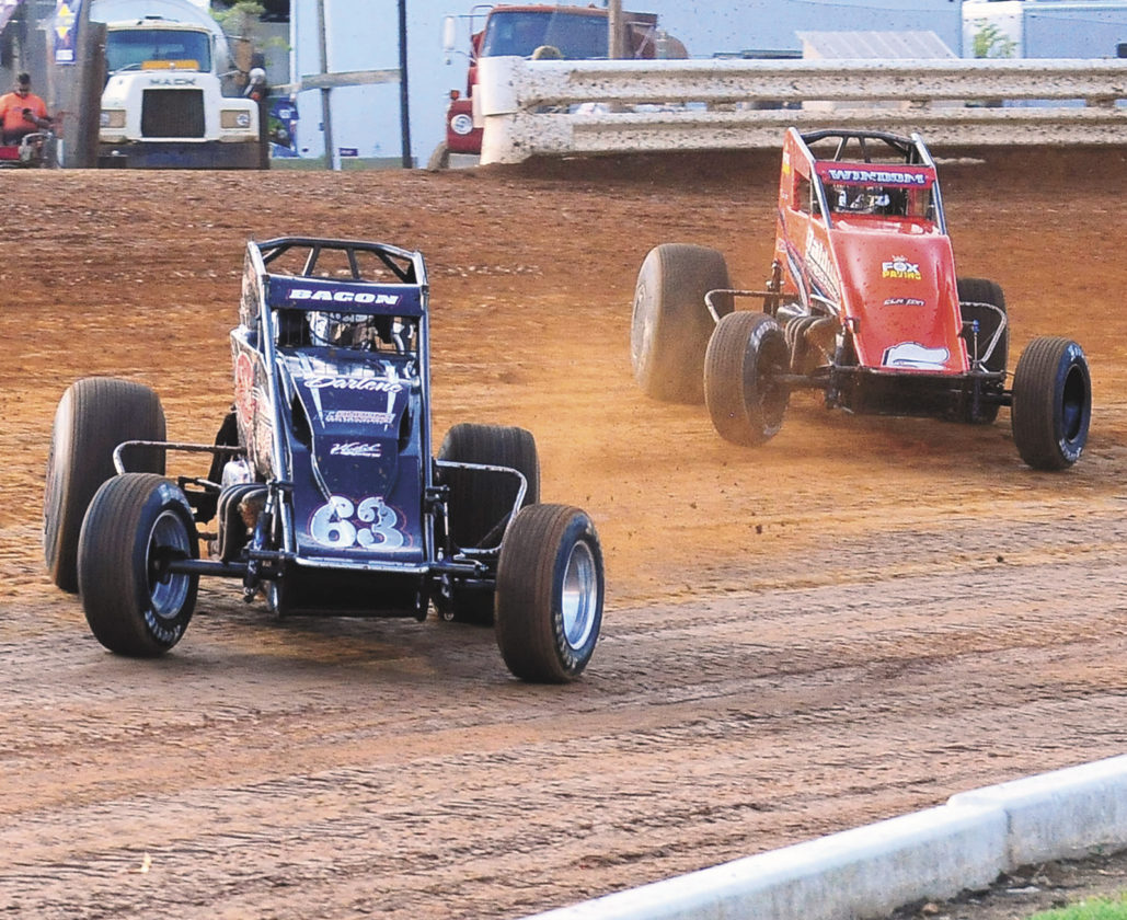 Sentinel photo by TIM SHUMAKER Coming around turn four are Brady Bacon (63) and USAC sprints Eastern Storm feature winner Chris Windom Saturday at Port Royal Speedway.
