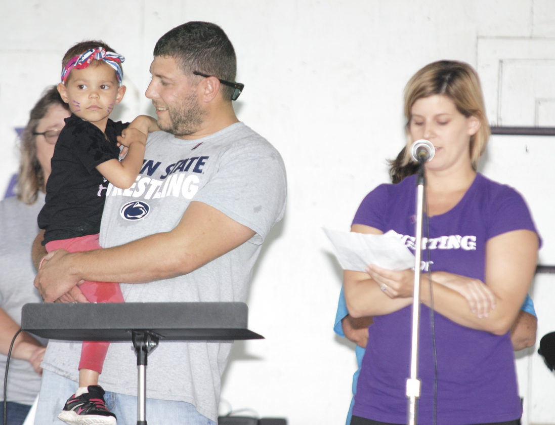 Sentinel photo by BRADLEY KREITZER Honorary co-chairperson Finley Snook, 4, left, is held by her father Colby Snook as her mother Casey Snook speaks during the Survivor Celebration at the 13th annual Midd-West Relay For Life Friday evening  in Beaver Springs. Finley was 3 years old when she was diagnosed with Pre B Cell Acute Lymphoblastic Leukemia. This year Finley was an honorary co-chair with Gary Saner.