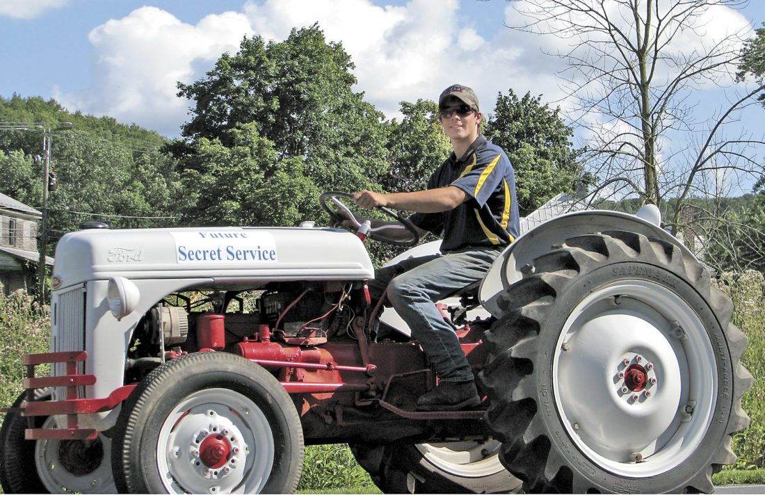 Sentinel photo by TABITHA GOODLING East Juniata High School FFA member Blake Sheaffer rides a tractor through the Dutch Days parade Saturday in Richfield. The FFA group featured several tractors and a float with the theme 'Secret Service.' The FFA entry was top winner at the parade.