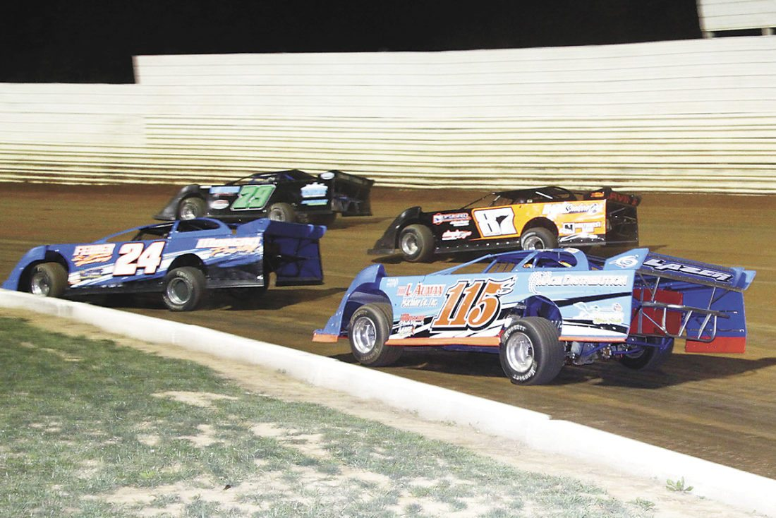 Sentinel photo by TIM SHUMAKER In the 25-lap Dave Kepner Tribute for econo late models, Eric Irvin (87) works his way through traffic against Shaun Miller (115s), Chase Bowsman (79) and Tim Fedder (24) on his way to victory lane.