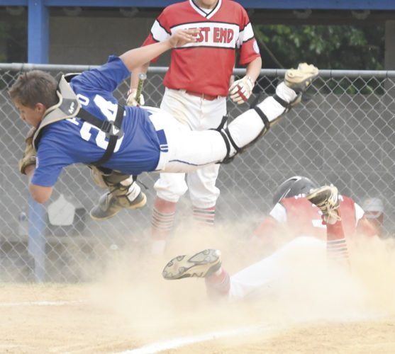 Sentinel photo by JEFF FISHBEIN  Mifflin County catcher Jaxson Pupo goes airborne trying to make a play against West End's Owen Anderson during the Babe Ruth 14-year-old state championship game Thursday in Lehighton.