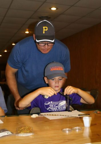 Sentinel photo by MATT STRICKER Camren Moore, 11, of Burnham, learns about fly tying from Trout Unlimited instructor Joe Hackenberg during the youth field day, sponsored by the Shade Mountain Chapter of the National Wildlife Turkey Federation.